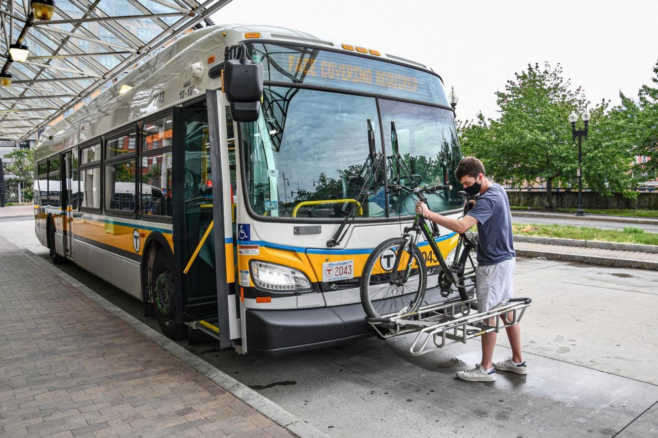 Man puts bike on MBTA bus rack