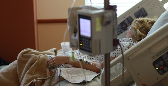 Woman in hospital bed with IV drip