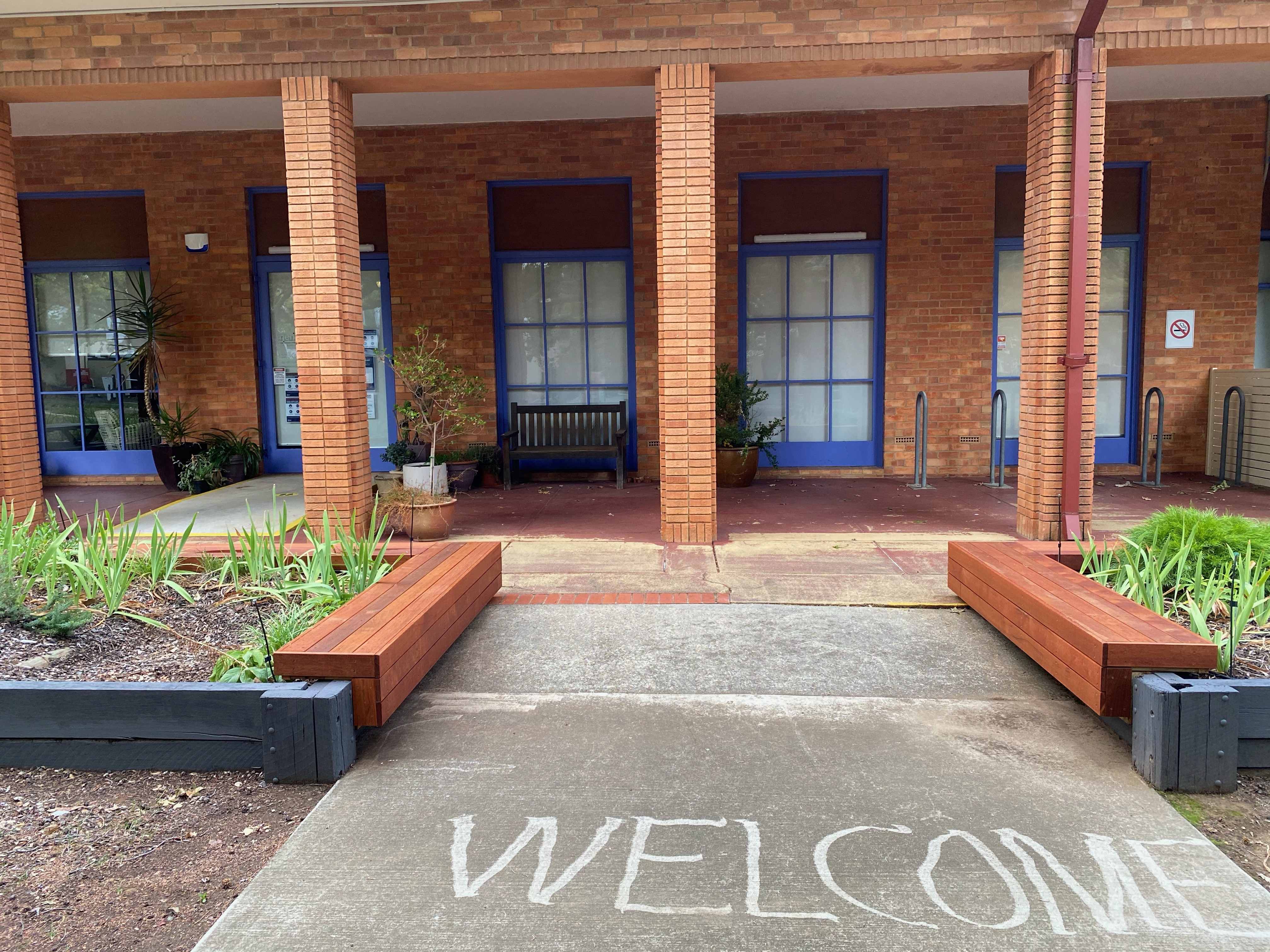"""Front entrant to Meridian building with """"Welcome"""" painted on the concrete footpath"""