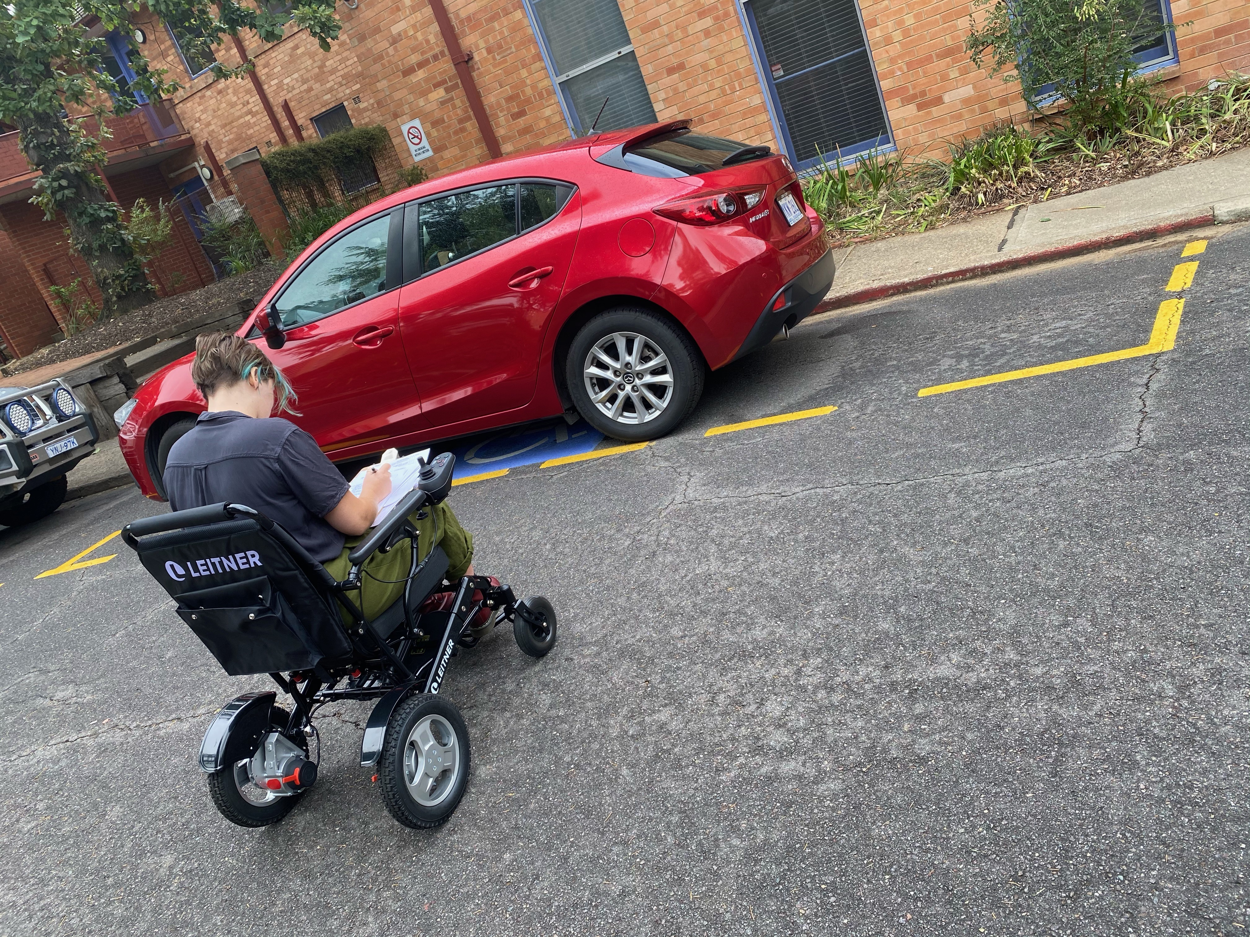 A woman in a wheelchair beside a disabled car parking space in the Meridian carpark
