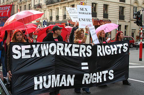 """[Image description: Sex workers protesting at a parade holding a banner that says """"sex workers rights = human rights""""]"""