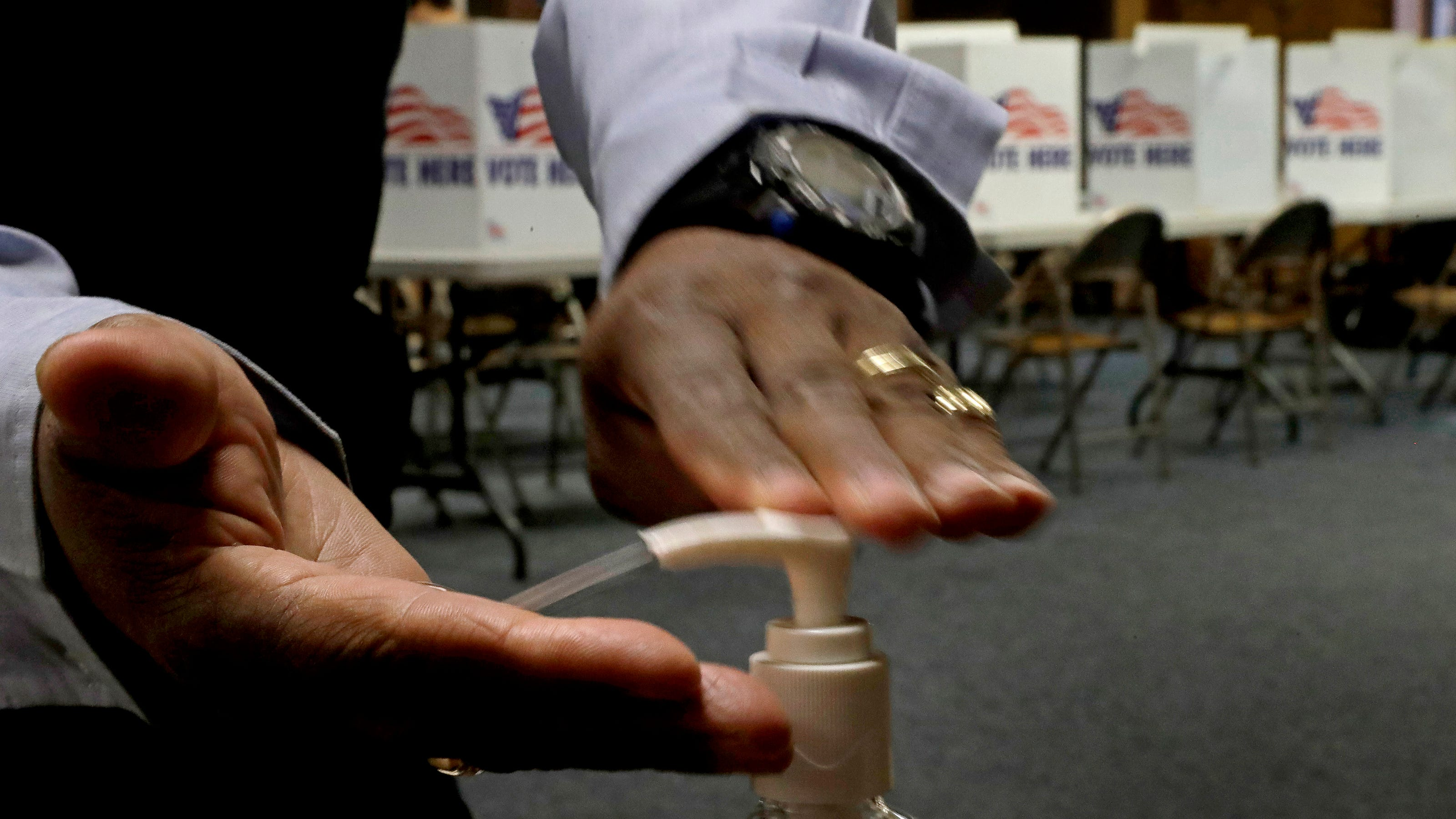Close-up of a man squirting sanitizer into his hands, with voting booths in the background