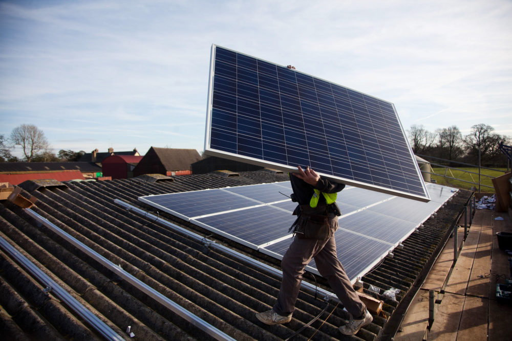 A worker installs solar panels on a barn roof.