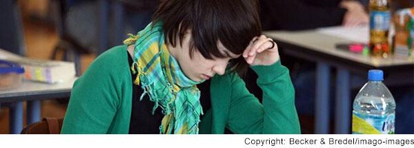 Eine Schülerin stützt ihren Kopf in die Hand, auf dem Tisch vor ihr sind ihre Prüfungsunterlagen und eine Flasche Wasser
