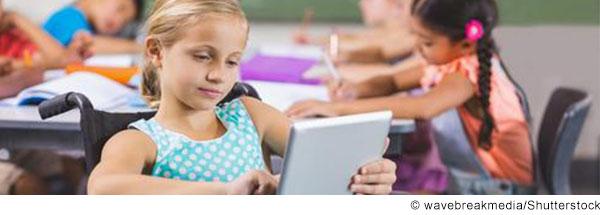 Mädchen im Rollstuhl sitzt im Klassenzimmer und arbeitet am Tablet.