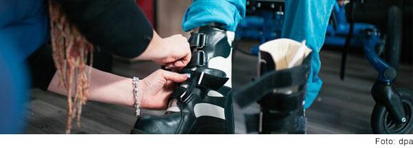 Einem Kind im Rollstuhl werden Schuhe angezogen