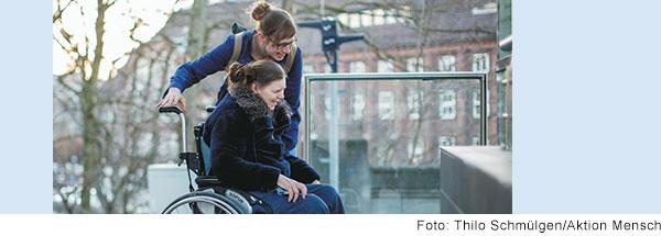 Frau schiebt Frau im Rollstuhl.