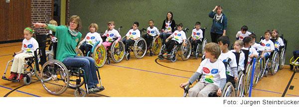 Kinder im Rollstuhl in einer Sporthalle