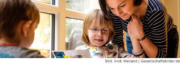Zwei Kinder sitzen an einem Tisch und machen Hausaufgaben. Eine Frau mit langen schwarzen Haaren beugt sich zu dem Mädchen mit Behinderung herunter.