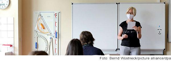 Lehrerin mit Mundschutz unterrichtet eine Klasse