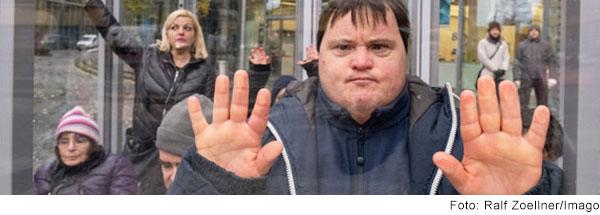 Eine Gruppe von Menschen mit Behinderung in einem Glaskäfig