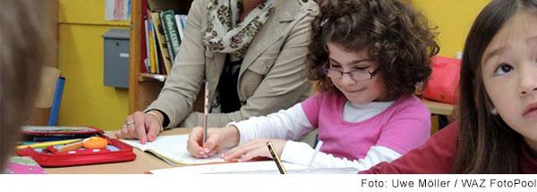 Zwei Mädchen sitzen nebeneinander am Tisch und schreiben in  Hefte. Neben ihnen sitzt eine junge Frau.