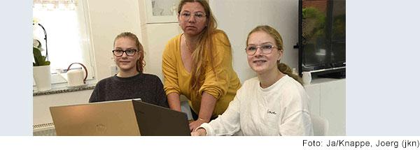 Drei junge Frauen sitzen an einem Tisch vor Laptops.
