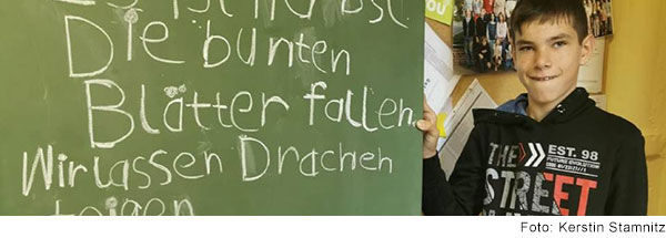 Schüler vor einer Tafel mit von ihm geschriebenen Text.
