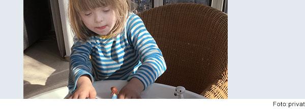 Junge mit Down-Syndrom spielt am Tisch mit Spielfiguren.