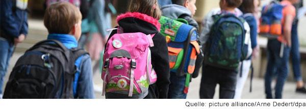 Schülerinnen und Schüler einer Grundschule stehen mit Abstand  zueinander auf dem Schulhof