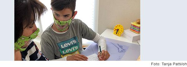 Junge mit Mundschutz sitzt an einem Schreibtisch mit  Matheaufgaben und spricht mit einer Frau, die neben ihm sitzt. Sie  trägt auch einen Mundschutz.