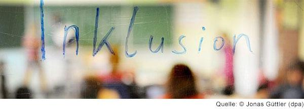 Unscharfes Bild eines Klassenzimmers mit Schülern. In blauer  Schrift hat jemand das Wort Inklusion auf das Bild geschrieben.