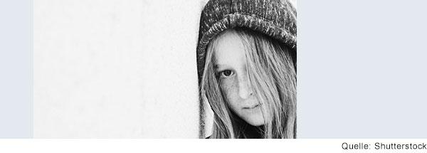 Mädchen mit langen Haaren und Mütze schaut traurig in die Kamera.