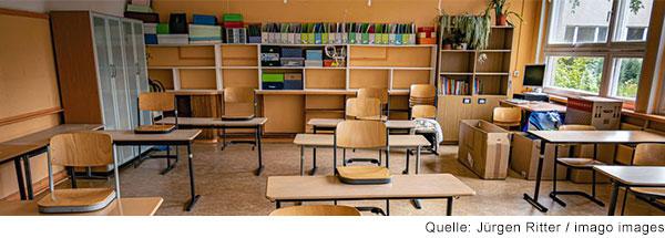 Leeres Klassenzimmer mit hochgestellten Stühlen.