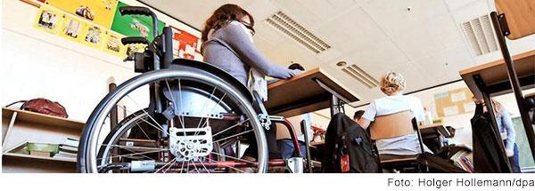 Jugendliche im Rollstuhl sitzt im Klassenzimmer am Tisch und arbeitet