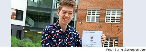 Der gehörlose Elias Louis Zander hält lachend sein Abiturzeugnis in die Kamera