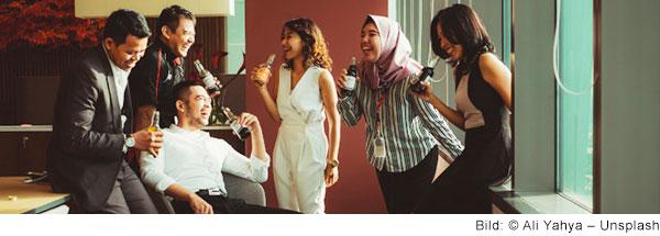 Eine Gruppe unterschiedlicher Menschen stehen lachend im Büro zusammen und haben Getränke in der Hand.