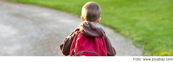 Junge im Grundschulalter von hinten mit großem roten Rucksack.