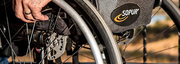 Räder von einem Rollstuhl mit Hand eines älteren Menschen.