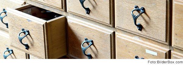 Holzschrank mit vielen kleinen Schubladen. Eine Schublade steht ein Stück offen.