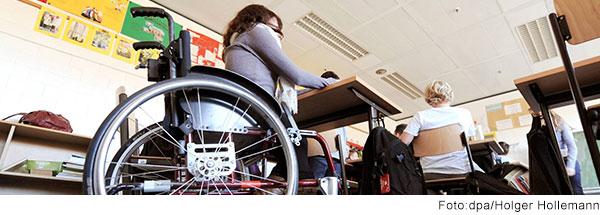Jugendliche sitzt im Rollstuhl an einem Tisch im Klassenzimmer
