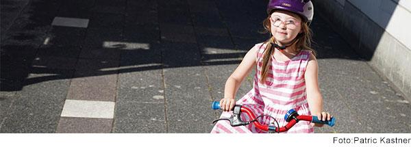 Mädchen mit Down-Syndrom im Grundschulalter sitzt mit lila Helm auf einem roten Fahrrad und lächelt in die Kamera.
