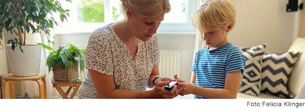 Eine Frau misst bei einem Jungen im Grundschulalter die Blutzuckerwerte.
