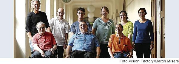 Gruppenbild von 9 Menschen. In der vorderen Reihe stehen 3 Männer in Rollstühlen. Hinter ihnen stehen 6 Menschen, 3 Männer und 3 Frauen.
