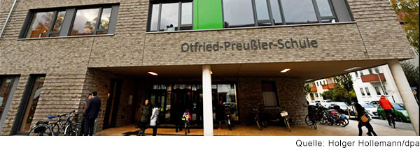 Eingang eines mit dunklem Klinker verkleideten Gebäudes, über dem der Schriftzug Otfried-Preußler-Schule steht.
