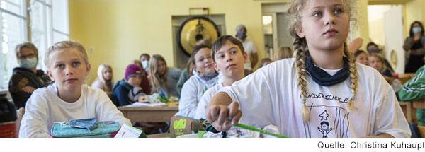 Blick in eine Schulklasse. Mehrere Kinder sitzen an einem Tisch und schauen nach vorne.