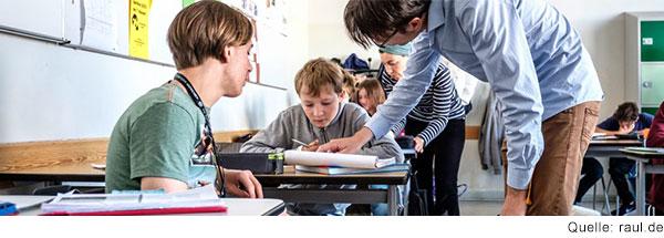 Blick in eine Schulklasse. An zwei Tischen stehen Erwachsene neben den Schüler:innen und erklären ihnen etwas.