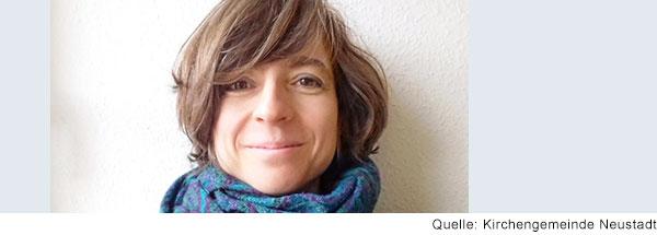 Portrait einer Frau mit dunklen mittellangen Haaren, die lächelnd in die Kamera schaut.