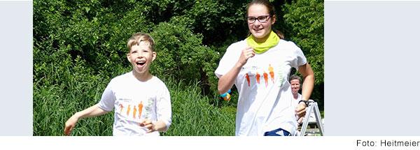 Ein Junge und ein Mädchen laufen nebeneinander. Sie haben die gleichen T-Shirts einen Lauftreffs an. Der Junge hat eine Behinderung.