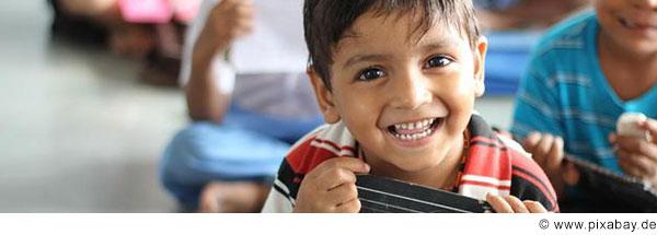 Ein Junge im Grundschulalter mit dunklen Augen und dunklen Haaren lacht in die Kamera.