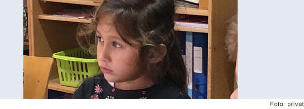 Mädchen im Grundschulalter mit dunklen langen zusammengebundenen Haaren sitzt an einem Tisch im Klassenzimmer und schaut in die Ferne.