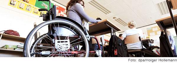 Jugendliche im Rollstuhl sitzt an einem Tisch im Klassenzimmer.