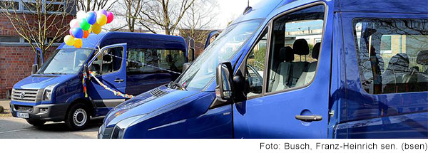 Zwei blaue Kleinbusse stehen vor einem Gebäude, einer der Busse ist mit einem Strauss bunter Luftballons geschmückt.