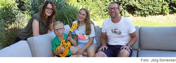 Familie Zerbe auf dem Garten-Sofa. Vorne sitzt der siebenjährige Maximilian mit Trisomie 21 und spielt auf einer gelben Gitarre. Links neben ihm sitzt seine ältere Schwester und sein Vater. Rechts neben ihm steht sein Mutter. Alle lachen in die Kamera.