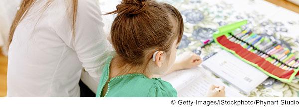 Mädchen mit Hörgerät sitzt am Tisch und schreibt in ein Schulheft. Eine junge Frau sitzt neben ihr und schaut ihr zu.