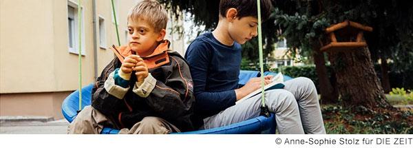 Zwei Jungen sitzen zusammen in einer Nestschaukel. Ein Junge liest in einem Buch, der andere Junge schaut in die Ferne. Er hat Down-Syndrom.