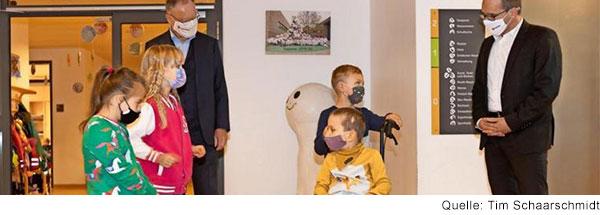 Zwei Männer in dunklen Anzügen stehen mit zwei Jungen und zwei Mädchen im Grundschulalter  im Flur einer Schule. Alle tragen einen Mundnasenschutz. Die Männer schauen auf einen Jungen, der den Rollstuhl des anderen Jungen schiebt und mit ihnen spricht.