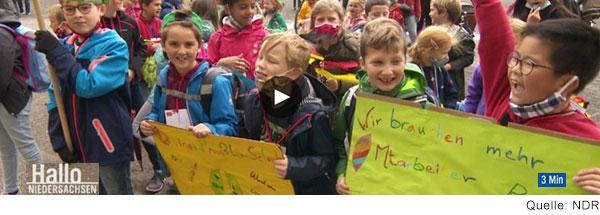 Grundschulkinder demonstrieren. Auf einem ihrer Plakate steht: Wir brauchen mehr Mitarbeiter.