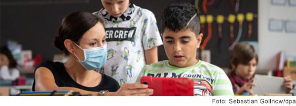 Ein Junge im Grundschulalter sitzt am Tisch im Klassenzimmer. Neben ihm sitzt eine junge Frau. Sie hält einen Tablet-Computer vor den Jungen. Hinter ihnen steht ein zweiter Junge. Alle schauen auf das Tablet.