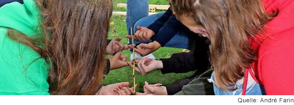 Jugendliche sitzen in der Hocke in zwei Reihen gegenüber. Alle halten einen Zeigefinger in die Mitte, worauf sie alle zusammen einen Meterstab balancieren.